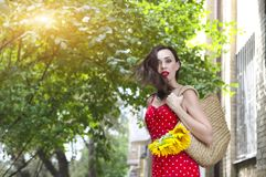 Beautiful young woman in red polka dots dress holding basket with sunflowers. Close up stock images