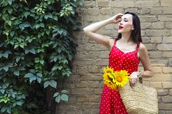 Beautiful young woman in red polka dots dress holding basket with sunflowers. Close up royalty free stock photos