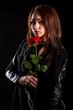 Beautiful young woman with a red rose in a black leather jacket Royalty Free Stock Photos