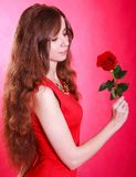 Beautiful young woman with a red rose. Over pink background Stock Image