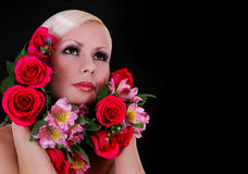 Beautiful young woman with red roses and pink irises in her hair over black Stock Photo