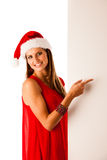 Beautiful young woman in red santa claus dress pointing to red b Royalty Free Stock Images