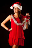 Beautiful young woman in red santa dress isolated over black bac Royalty Free Stock Images