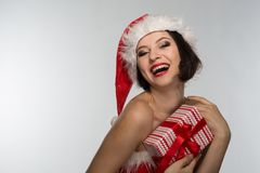 Beautiful young woman in a red skirt and santa claus hat celebra Stock Images