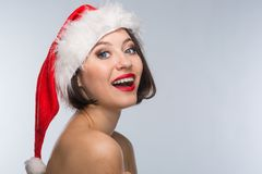 Young woman in a red skirt and santa claus hat on a light backgr Stock Image