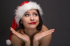Young woman in a red skirt and santa claus hat on a light backgr Royalty Free Stock Photos