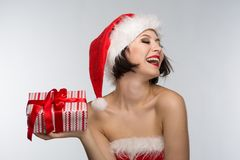 Beautiful young woman in a red skirt and santa claus hat celebra Stock Image