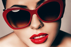 Beautiful young woman in red sunglasses stock photos