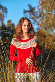 Beautiful young woman in red sweater in park Stock Photography