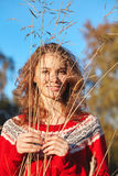 Beautiful young woman in red sweater in park Royalty Free Stock Photography