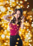 Woman and sparkles. Beautiful young woman in red tank top and hat posing for camera while standing on sparkles background stock images