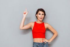 Beautiful young woman in red top pointing finger up Royalty Free Stock Images