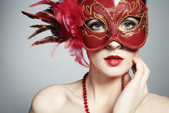 The beautiful young woman in a red venetian mask Stock Image
