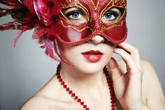 The beautiful young woman in a red venetian mask Stock Photography
