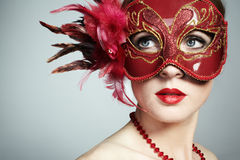 The beautiful young woman in a red venetian mask Royalty Free Stock Photo