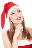 Beautiful young woman in red wearing santa hat. Royalty Free Stock Images
