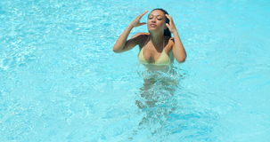 Beautiful Young Woman Refreshing at Swimming Pool stock video footage