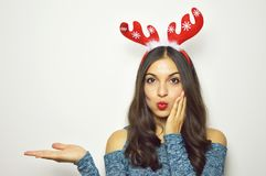 Beautiful young woman with reindeer horns on her head looks at camera and presenting your product on white background. Copy space. Royalty Free Stock Photos