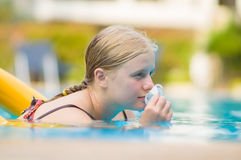 Beautiful young woman relax on life ring in pool with Frangipani Royalty Free Stock Photo