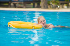 Beautiful young woman relax on life ring in pool in tropical bea Royalty Free Stock Photo