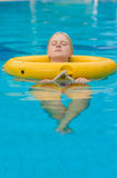 Beautiful young woman relax on life ring in pool in tropical bea Royalty Free Stock Image