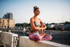 Beautiful young woman relax in yoga pose. City on background. Yogi meditation exercise outdoors Royalty Free Stock Photo