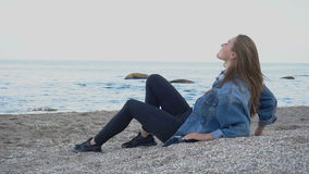 Beautiful young woman relaxes sitting on beach and enjoys view of sea and sky on warm summer evening. stock video footage