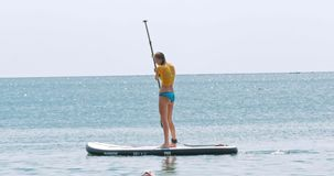 Beautiful young woman relaxes on a SUP board stock video