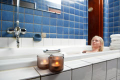 Beautiful young woman relaxing in bathtub. With candles in foreground Royalty Free Stock Images