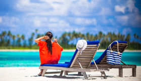 Beautiful young woman relaxing at beach chairs. Back view of young beautiful woman relaxing at beach chairs Royalty Free Stock Photography