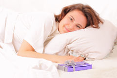 Beautiful young woman relaxing in bed with a gift Stock Photo