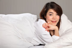 Beautiful young woman relaxing in bed smiling Royalty Free Stock Images