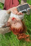 Beautiful young woman relaxing with camera in her hand on garden bench in green grass Royalty Free Stock Photo