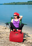 Beautiful young woman relaxing in a chair near the lake Stock Photos