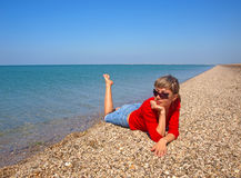 Beautiful young woman relaxing on a coastline Stock Photo