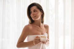 Beautiful young woman relaxing at cozy home atmosphere next to w. Indow. Caucasian woman wearing white towel with cup of hot chocolate or coffee in her hands Royalty Free Stock Image
