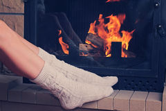 A beautiful young woman  and relaxing enjoying near a fireplace. Cozy winder. Christmas  holidays concept. Stock Photography