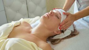 Beautiful young woman relaxing with face massage at luxury spa salon, close-up. stock photos