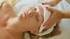 Beautiful young woman relaxing with face massage at luxury spa salon, close-up. stock images