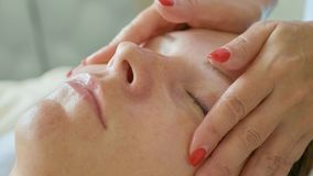 Beautiful young woman relaxing with face massage at luxury spa salon, close-up. royalty free stock image