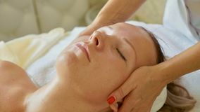 Beautiful young woman relaxing with face massage at luxury spa salon, close-up. Royalty Free Stock Images