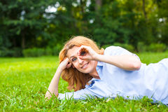 Beautiful young woman relaxing in grass Stock Photography