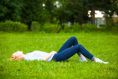 Beautiful young woman relaxing in grass Royalty Free Stock Photo
