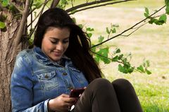 Beautiful young woman relaxing on grass with smart phone Stock Image