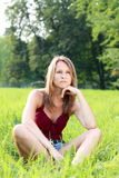 Beautiful young woman relaxing on green grass Royalty Free Stock Photos