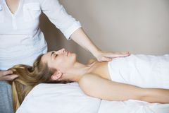 Beautiful young woman relaxing with hand massage at beauty spa royalty free stock image