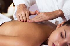 Beautiful young woman relaxing with hand massage at beauty spa. Royalty Free Stock Image
