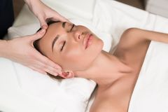 beautiful young woman relaxing and having head massage stock image