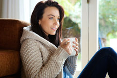 Beautiful young woman relaxing at home with a cup of coffee Royalty Free Stock Photography