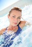 Beautiful young woman relaxing in jacuzzi Stock Photos